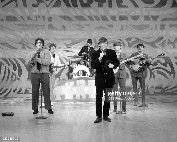 The Turtles perform Happy Together on The Ed Sullivan Show on Sunday, May 14, 1967. L-R Mark Volman (with trumpet); Jim Pons (bass guitar); John Barbata (on drums); Howard Kaylan (lead singer); Al Nichol (guitar) and Jim Tucker (guitar, far right).